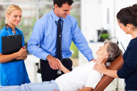 health professionals: friendly male doctor greeting senior patient before medical checkup
