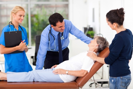 patient in bed: friendly male doctor talking to senior patient before examining