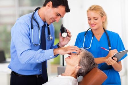 ophthalmologist: male ophthalmologist examining senior womans eye Stock Photo