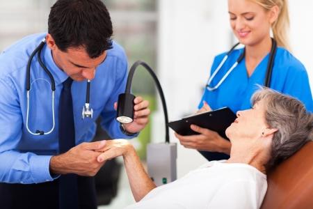 inspecting: dermatologist examining senior womans skin under light