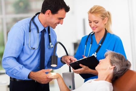 dermatologo: dermatologo e asssistant registrazione anziano condizione della pelle del paziente dopo l'esame