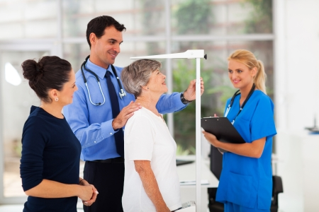 general practitioner measuring senior patients height in office photo