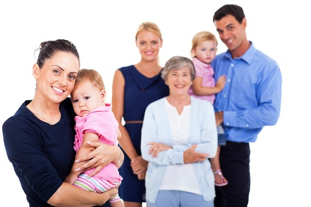 extended family: portrait of young woman holding her baby with extended family on background
