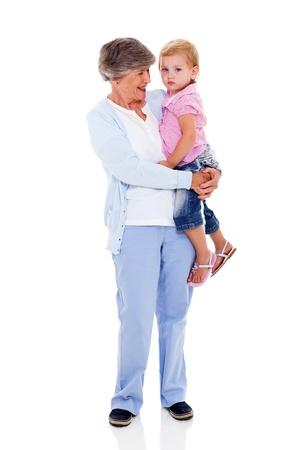 senior woman: full length portrait of grandmother carrying her grandchild isolated on white Stock Photo