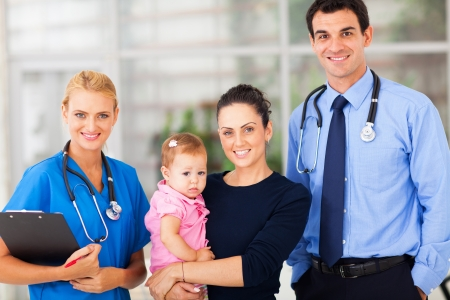 office visit: young woman holding her baby standing with doctor and female nurse in hospital Stock Photo