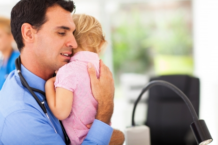 sick baby: caring pediatrician hugging a sick baby girl