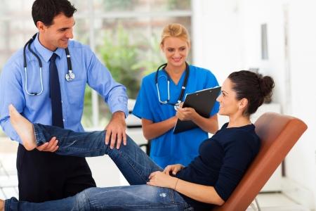 orthopaedist: orthopaedist examining female patients leg with nurse in office