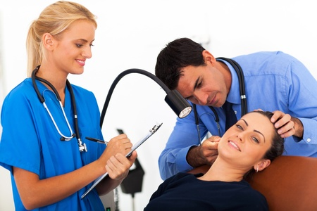 doctor examining womans ear with nurse photo