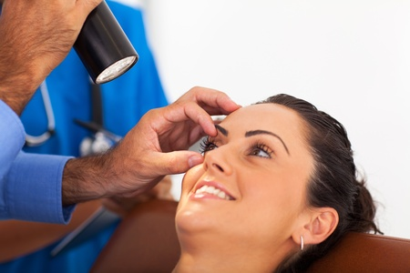 office visit: woman in for eye check up in doctors office Stock Photo