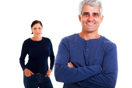 happy couple white background: smiling middle aged man with arms folded with his wife on background