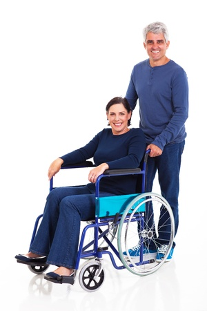 smiling middle aged man pushing handicapped wife on wheelchair isolated on white background photo