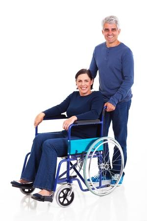 hombre empujando: sonriente hombre de mediana edad empuja a la esposa para minusv�lidos en silla de ruedas aisladas sobre fondo blanco Foto de archivo