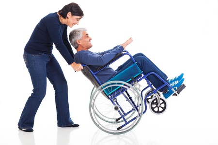 funny love: happy mature couple having fun with wheelchair isolated on white background Stock Photo