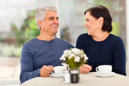 mid adult couple: happy laughing middle aged couple enjoying tea at home