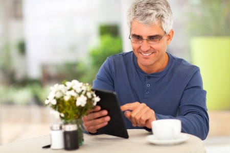 ged: smiling middle ged man surfing the internet using tablet computer at home