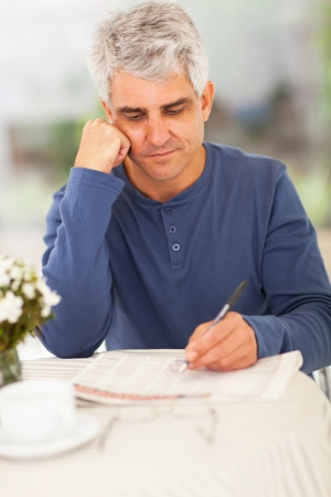 handsome middle aged man going through classified on newspaper photo