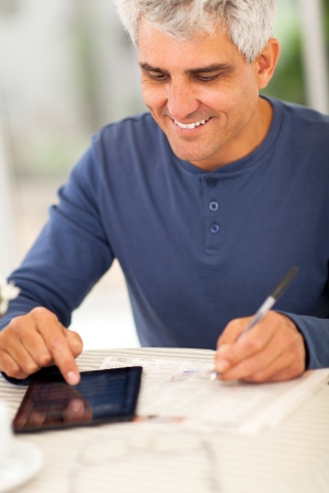 middle aged man reading newspaper and making notes on tablet computer photo