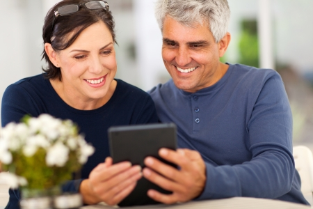 middle aged couple reading emalis on tablet computer photo