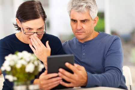 middle aged couple reading shocking news on tablet computer photo