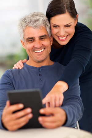 smile close up: happy senior couple using tablet computer at home