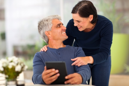 lovely couple: beautiful loving middle aged couple with tablet computer