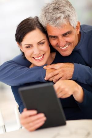 mujeres maduras: Encantadora pareja madura con tablet PC en casa Foto de archivo