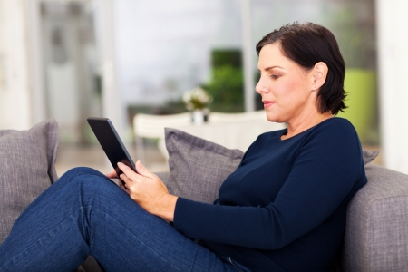 old sofa: attractive mature woman using tablet computer at home