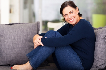 middle aged: cheerful middle aged woman relaxing on a sofa