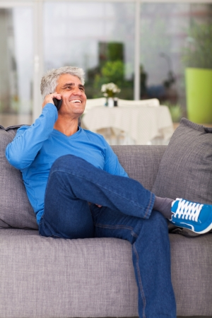 happy middle aged man talking on cell phone at home
