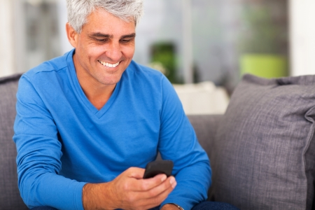 cheerful middle aged man reading emails on smart phone photo