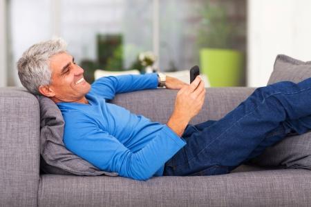 mann couch: Mann mittleren Alters, liest SMS auf Handy beim Liegen auf der Couch