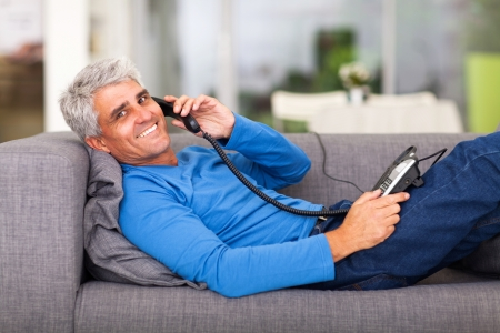 cheerful middle aged man talking on the telephone while lying on sofa photo
