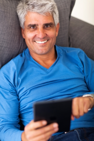 overhead portrait of mature man using tablet computer while lying on sofa photo