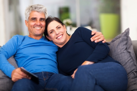beautiful loving middle aged couple sitting on sofa  photo