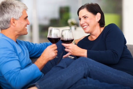 cheerful middle aged couple enjoying wine at home photo