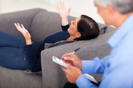 psychologist: middle aged woman lying on sofa and talking to her psychologist