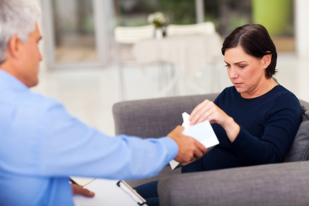 counselling: understanding therapist handing tissue to an upset middle aged patient