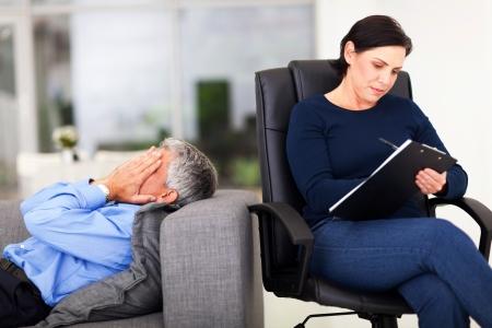 terapia psicologica: hombre de mediana edad llorando durante la sesión con el terapeuta en la oficina