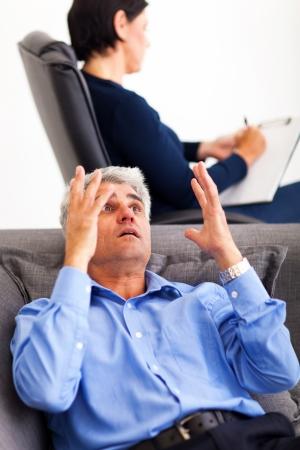 psychologist: mature middle aged man explaining his problem to psychologist