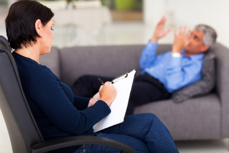 shrink: middle aged female psychologist making note while patient talking Stock Photo