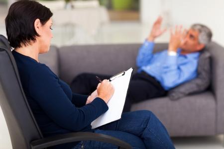 psicóloga de mediana edad tomando nota mientras el paciente habla Foto de archivo