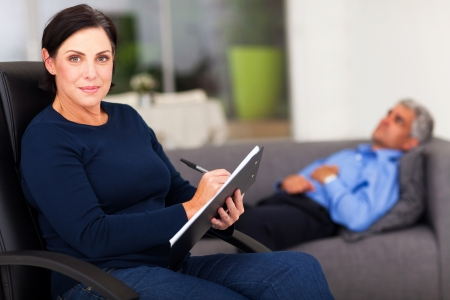 female therapist: portrait of middle aged female therapist in office with patient in background Stock Photo