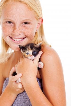 pre adolescence: happy little girl holding kitten isolated on white