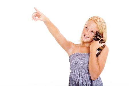 beautiful teen girl holding pet kitten and pointing on copyspace photo