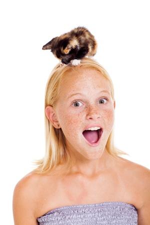 pre adolescence: little pet kitten sitting on teen girls head