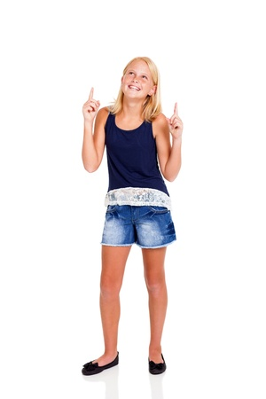 happy pre teen girl pointing up isolated on white photo