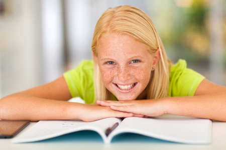 pre adolescents: happy teen girl lying on book at home Stock Photo