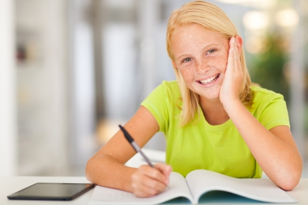 happy teen schoolgirl doing homework at home photo
