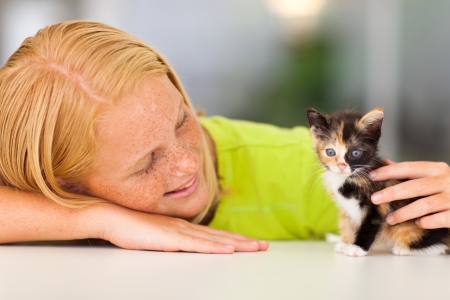 loving pre teen girl playing with her pet kitten Stock Photo