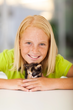 pre teen girl: caring teen girl playing with pet kitten at home Stock Photo